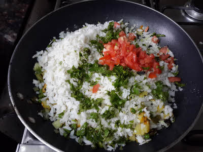 Add soaked pohe, fresh coriander leaves and tomatoes