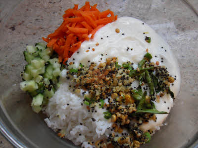 In a big bowl add steamed rice, grated carrots, chopped cucumber, salt and the mustard seeds tempering