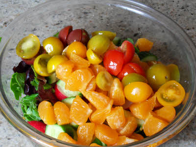 Cut tomatoes and lettuce for mandarin salad